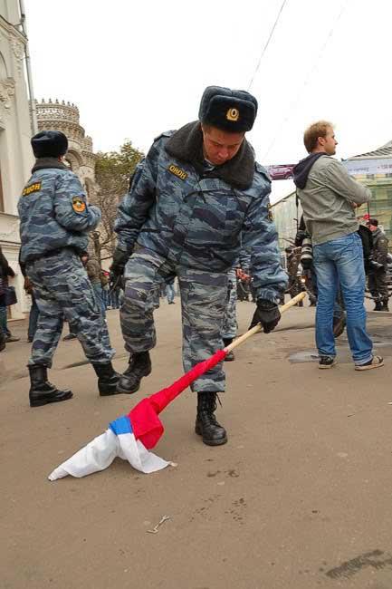 Российский милиционер попирает ногами флаг РФ